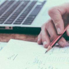 Man writing near open laptop